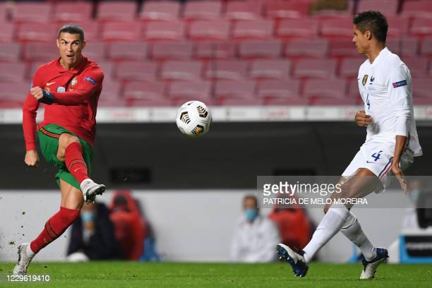 Portugal's forward Cristiano Ronaldo shoots next to France's defender Raphael Varane during the UEFA Nations League A group 3 football match between...