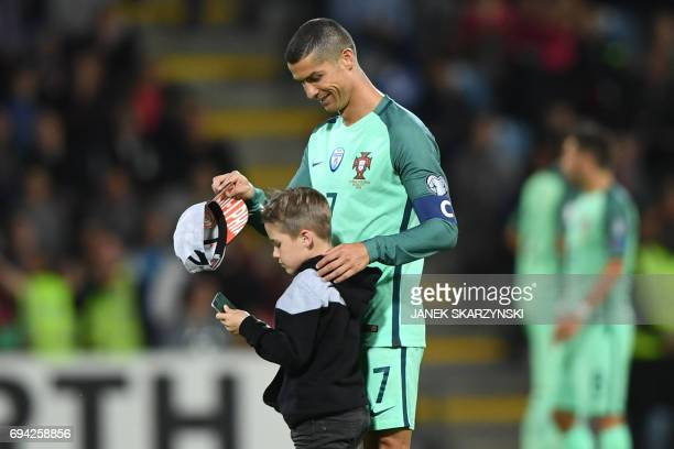 Portugal's forward Cristiano Ronaldo speaks to a child after the FIFA World Cup 2018 qualification football match between Latvia and Portugal in Riga...