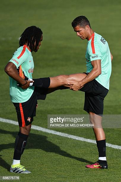 Portugal's forward Cristiano Ronaldo stretches helped by Portugal's midfielder Renato Sanches during a training session in preparation for the Euro...
