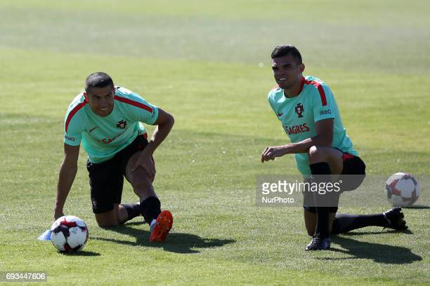 Portugal's forward Cristiano Ronaldo stretches with Portugal's defender Pepe during a training session at quotCidade do Futebolquot training camp in...