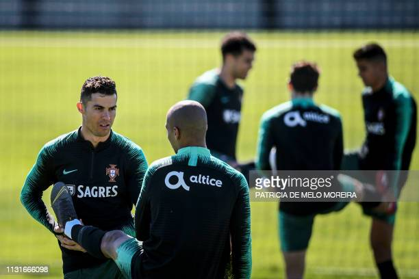 Portugal's forward Cristiano Ronaldo stretches with Portugal's midfielder Joao Mario during a training session at City of Football training camp in...