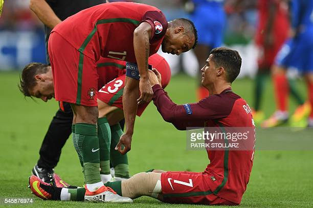 Portugal's forward Cristiano Ronaldo talks with Portugal's forward Nani as he sits injured on the pitch during the Euro 2016 final football match...