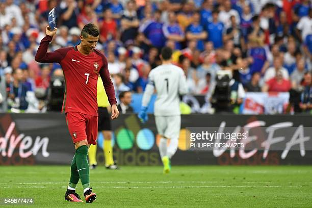 Portugal's forward Cristiano Ronaldo throws his captain's armband on the pitch after being injured during the Euro 2016 final football match between...