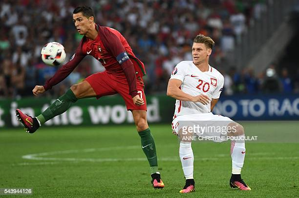TOPSHOT Portugal's forward Cristiano Ronaldo vies for the ball with Poland's defender Lukasz Piszczek during the Euro 2016 quarterfinal football...