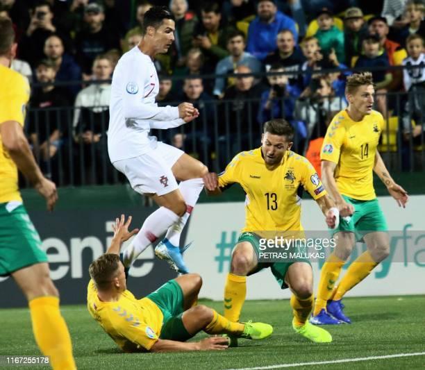Portugal's forward Cristiano Ronaldo vies with Lithuania's Saulius Mikoliunas during the UEFA Euro 2020 Group B qualification football match...