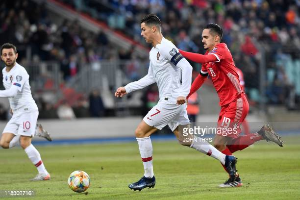 Portugal's forward Cristiano Ronaldo vies with Luxembourg's defender Aldin Skenderovic during the UEFA Euro 2020 Group B qualification football match...