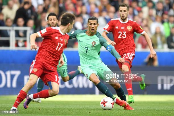 Portugal's forward Cristiano Ronaldo vies with Russia's midfielder Alexander Golovin and Russia's defender Dmitriy Kombarov during the 2017...
