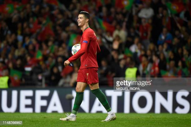 Portugal's forward Cristiano Ronaldo walks off the pitch with the match ball after scoring a hat-trick during the UEFA Nations League semi-final...