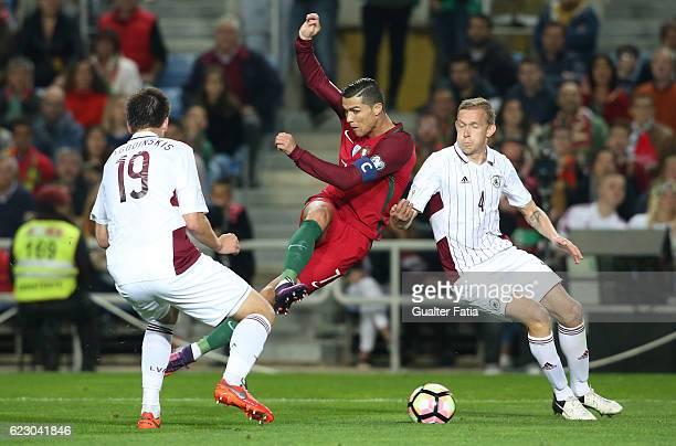 Portugal's forward Cristiano Ronaldo with Latvia's defender Vladislav Freimanis from Latvia and Latvia's defender Vitalis Jagodinskis from Latvia in...