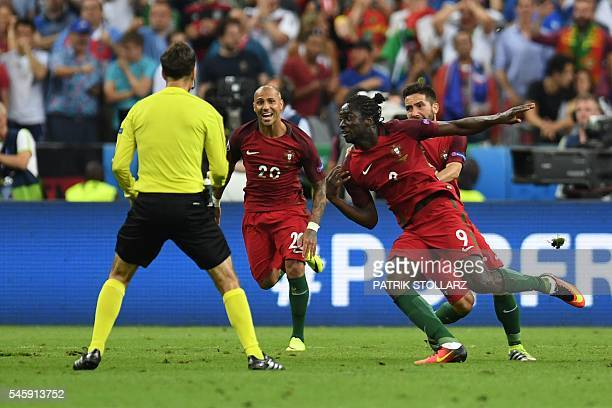 Portugal's forward Eder celebrates with teammates after he scored during the Euro 2016 final football match between Portugal and France at the Stade...