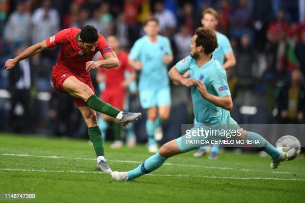 Portugal's forward Goncalo Guedes shoots to score the opening goal with Portugal's forward Bernardo Silva during the UEFA Nations League final...