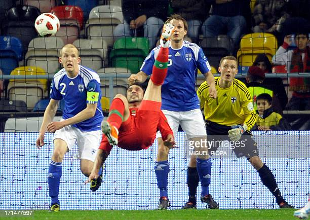 Portugal's forward Hugo Almeida kicks the ball close to Finland's Petri Pasanen, Jukka Raitala and goalkeeper Otto Fredrikson during their friendly...