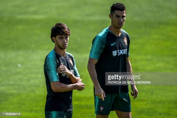 TOPSHOT Portugal's forward Joao Felix flanked by Portugal's forward Cristiano Ronaldo attend a training session at Cidade do Futebol training camp in...