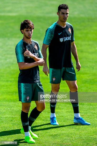 Portugal's forward Joao Felix flanked by Portugal's forward Cristiano Ronaldo attend a training session at Cidade do Futebol training camp in Oeiras...