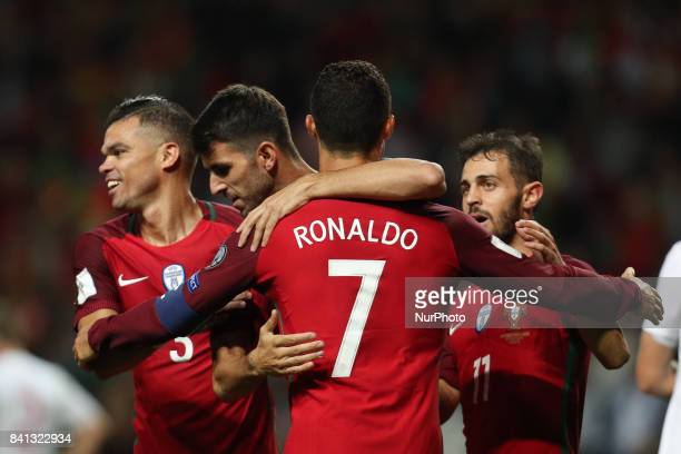 Portugal's forward Nelson Oliveira celebrates after scoring a goal with Portugal's forward Cristiano Ronaldo and Portugal's defender Pepe during the...