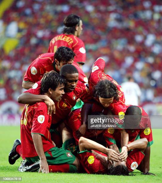 Portugal's forward Nuno Gomes is congratulated by his teammates after scoring the opening goal, 20 June 2004 at Jose Alvalade stadium in Lisbon,...