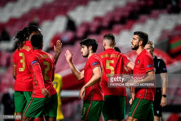 Portugal's forward Pedro Neto celebrates with teammates after scoring a goal during the international friendly football match between Portugal and...