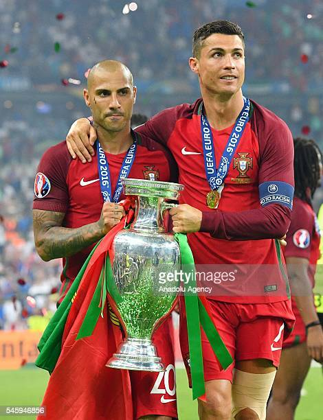 Portugal's forward Ricardo Quaresma and Portugal's forward Cristiano Ronaldo pose with the trophy on the pitch after they won the Euro 2016 final...