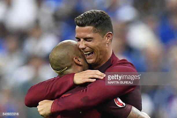 TOPSHOT Portugal's forward Ricardo Quaresma hugs Portugal's forward Cristiano Ronaldo after Portugal beat their hosts France 10 in the Euro 2016...