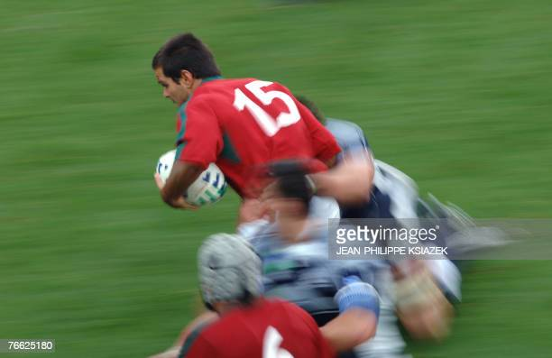 Portugal's fullback Pedro Leal is tackled by an unidentified Scottish player during the rugby union World Cup match Scotland vs Portugal, 09...