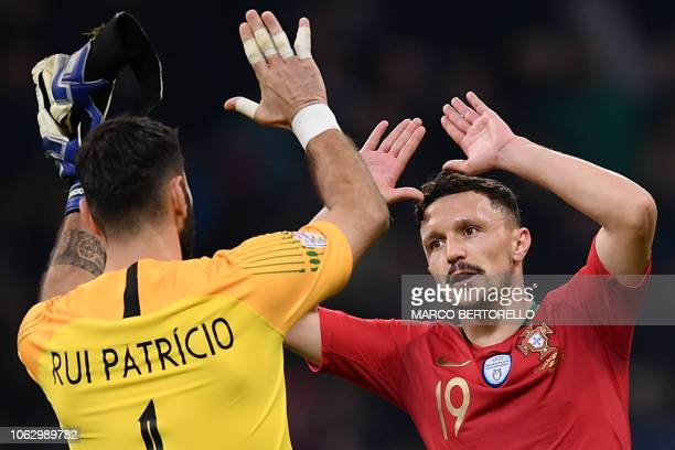 Portugal's goalkeeper Rui Patricio celebrates with Portugal's defender Mario Rui at the end of the UEFA Nations League group 3 football match Italy...