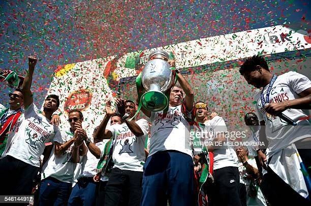 Portugal's head coach Fernando Santos holds the trophy as he celebrates with his players on a stage at Alameda square in Lisbon on July 11 2016 where...