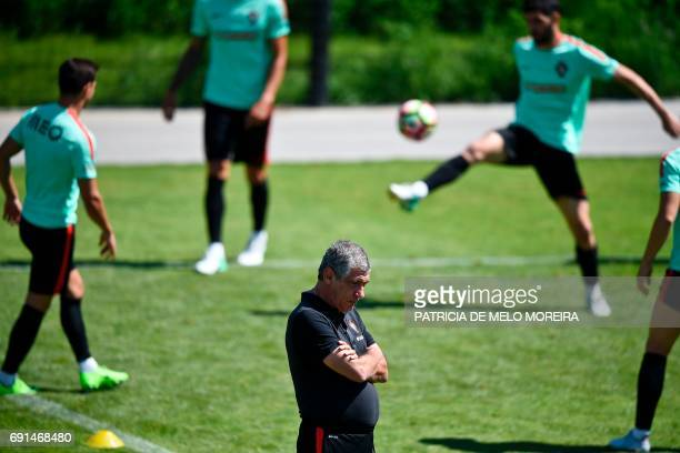 Portugal's head coach Fernando Santos looks down as players train during a training session at Cidade do Futebol training camp in Oeiras outskirts of...