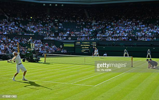 Portugal's Joao Sousa serves to Switzerland's Stan Wawrinka during their men's singles first round match on day one of the 2015 Wimbledon...