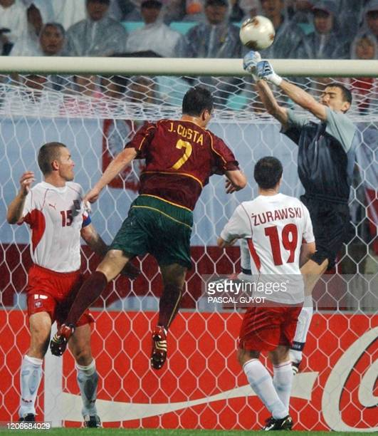 Portugal's Jorge Costa gets past Polish defenders Tomasz Waldoch and Maciej Zurawski to challenge Polish 'keeper Jerzy Dudek , 10 June 2002 at the...