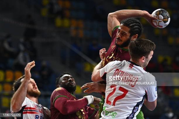 Portugal's left back Andre Gomes shoots challnged by Norway's right back Harald Reinkind during the 2021 World Men's Handball Championship between...