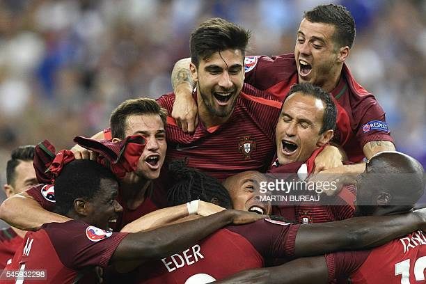 Portugal's midfielder Andre Gomes top celebrates with teammates Portugal's defender Ricardo Carvalho celebrate after beating their hosts France 10 in...