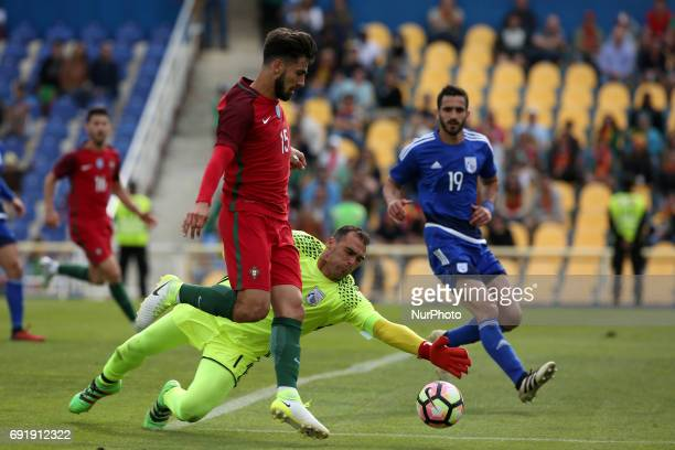 Portugal's midfielder Andre Gomes vies with Cypruss goalkeeper Antonis Giorgallidis during the friendly football match Portugal vs Cyprus at Antonio...