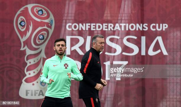 Portugal's midfielder Bernardo Silva runs with a staff member during a training session in Kazan Russia on June 27 2017 on the eve of the Russia 2017...