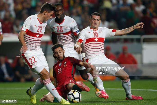 Portugal's midfielder Bernardo Silva vies for the ball with Switzerland's defender Fabian Schar and Switzerland's midfielder Granit Xhaka and...