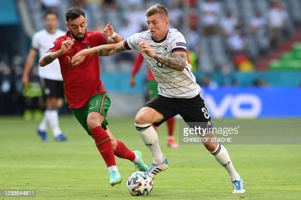 Portugal's midfielder Bruno Fernandes challenges Germany's midfielder Toni Kroos during the UEFA EURO 2020 Group F football match between Portugal...