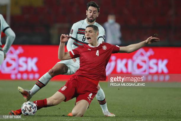 Portugal's midfielder Bruno Fernandes fights for the ball with Serbia's defender Nikola Milenkovic during the FIFA World Cup Qatar 2022 qualification...