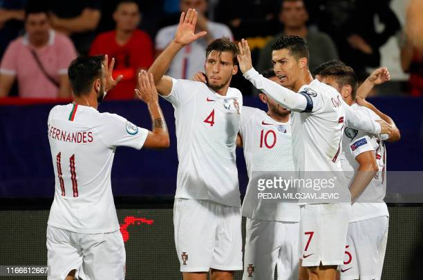 Portugal's midfielder Bruno Fernandes Portugal's defender Ruben Dias and Portugal's forward Cristiano Ronaldo celebrate a goal during the EURO 2020...