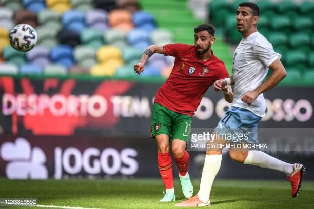 Portugal's midfielder Bruno Fernandes shoots next to Israel's defender Eytan Tibi during the international friendly football match between Portugal...