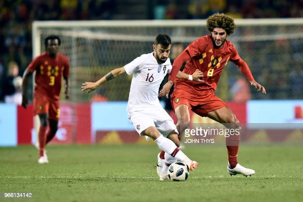 TOPSHOT Portugal's midfielder Bruno Fernandes vies with Belgium's midfielder Marouane Fellaini during the friendly football match between Belgium and...