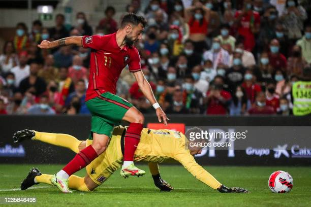 Portugal's midfielder Bruno Fernandes vies with Luxembourg's goalkeeper Anthony Moris during the FIFA World Cup Qatar 2022 qualification Group A...