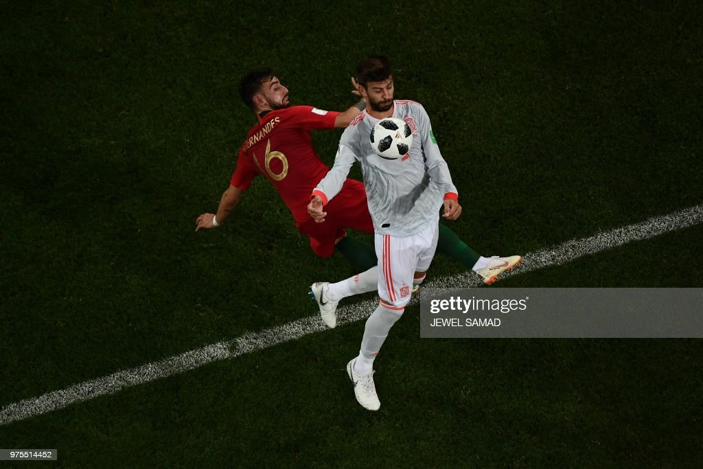 TOPSHOT - Portugal's midfielder Bruno Fernandes (L) vies with Spain's defender Gerard Pique (R) during the Russia 2018 World Cup Group B football match between Portugal and Spain at the Fisht Stadium in Sochi on June 15, 2018. (Photo by Jewel SAMAD / AFP) / RESTRICTED