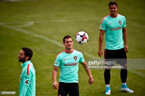 Portugal's midfielder Cedric Soares eyes the ball past Portugal's forward Andre Silva and Portugal's midfielder Joao Moutinho during a training...