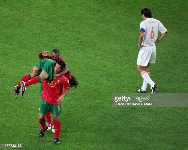Portugal's midfielder Costinha defender Ricardo Carvalho and defender Fernando Couto celebrate as Dutch captain Phillip Cocu looks dejected 30 June...