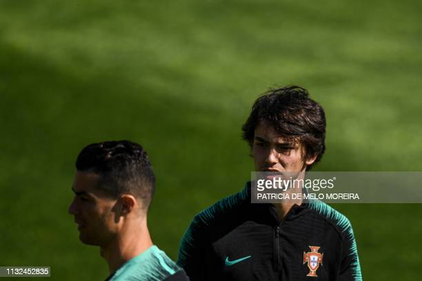 Portugal's midfielder Joao Felix passes by Portugal's forward Cristiano Ronaldo during a training session at Portugal's training camp Cidade do...