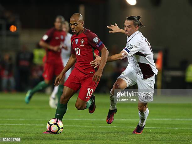 Portugal's midfielder Joao Mario with Latvia's defender Igor Tarasov from Latvia in action during the FIFA 2018 World Cup Qualifier match between...
