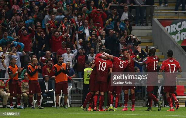 Portugal's midfielder Joao Moutinho celebrates with Portugal's forward Cristiano Ronaldo and teammates after scoring the winning goal during the UEFA...