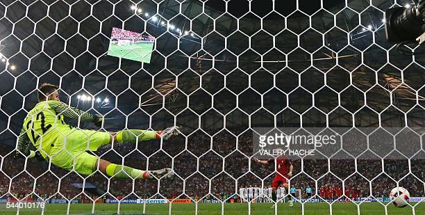 Portugal's midfielder Joao Moutinho scores in a penalty shootout during the Euro 2016 quarterfinal football match between Poland and Portugal at the...