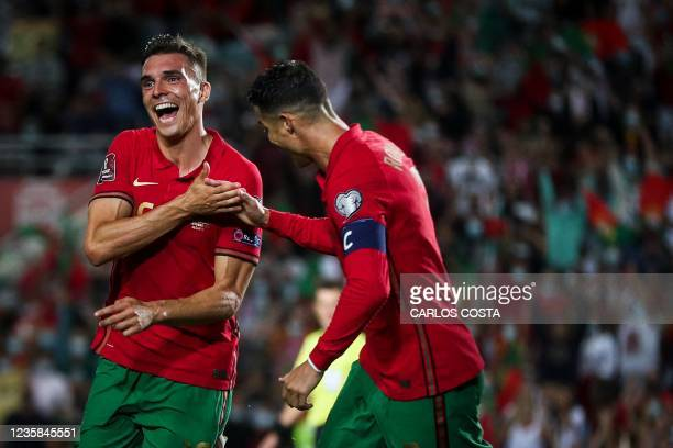 Portugal's midfielder Joao Palhinha celebrates with Portugal's forward Cristiano Ronaldo after scoring a goal during the FIFA World Cup Qatar 2022...