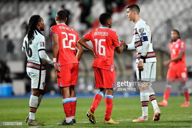 Portugal's midfielder Renato Sanches and Portugal's forward Cristiano Ronaldo shake hands with Luxembourg's defender Marvin Martins and Luxembourg's...