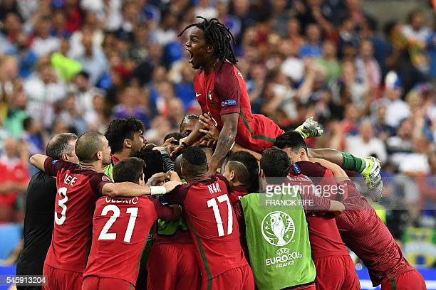 Portugal's midfielder Renato Sanches jumps on teammates after Portugal's forward Eder scored the first goal of the match during the Euro 2016 final...